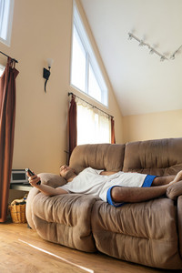Lazy or overtired man laying on the couch with the tv remote in his hand.