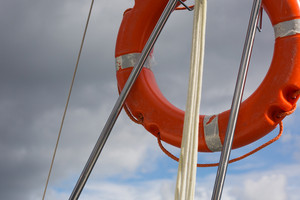 Lifebuoy hanging on back part of yacht with cloudy sky on background.