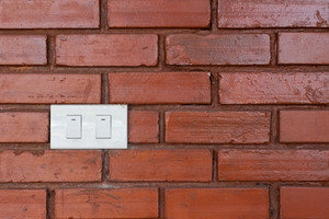 Light switch on red brick wall