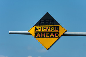 Light up roadway sign that tells when there is a red traffic signal ahead.