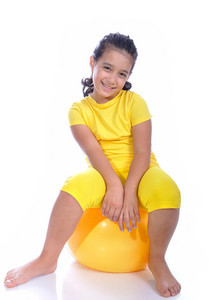 Little beautiful girl in yellow with yellow ball