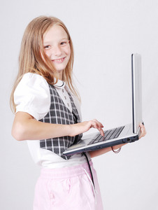 little blond school girl playing on internet standing  with laptop computer isolated