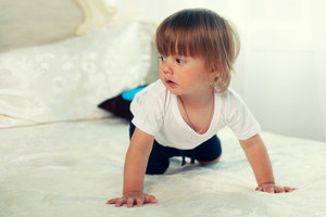 Little boy crawling on the big bed