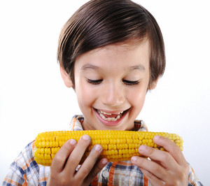 Little boy eating corn