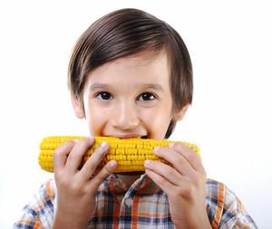 Little boy eating corn