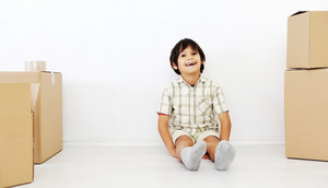 Little boy in a room of moving boxes looking at camera