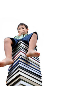 Little boy sitting on books isolated in white