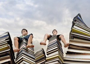 Little boy sitting on large stack of books