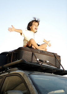 Little boy traveling on bags, the top of the car
