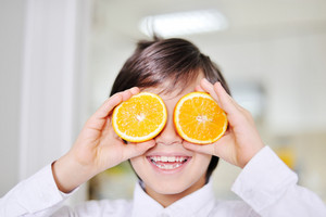 Little boy using oranges as glasses