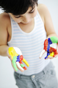 Little boy with hands painted in colorful paints ready for hand prints