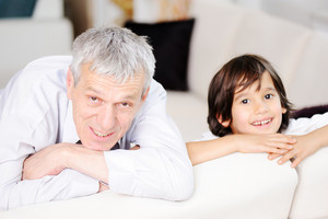 Little boy with his grandfather at home looking on the camera