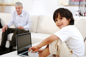 Little boy with his grandfather at home using laptop