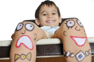Little boy with painted smileys on his legs
