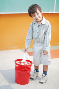 Little cute boy throwing paper in recycle bin