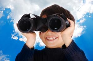 Little cute child with binoculars outdoor