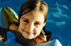 Little cute  girl  in blue water of the swimming pool, summer time for fun
