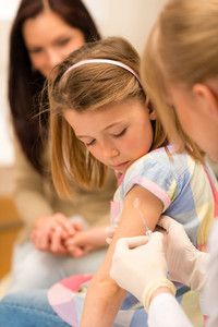 Little girl getting vaccination from pediatrician at medical office