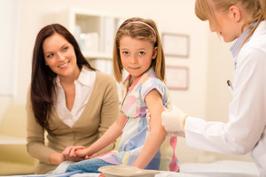 Little girl getting vaccination from pediatrician at office