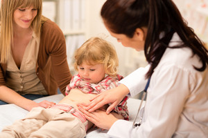 Little girl having tummy examination by pediatrician at medical office