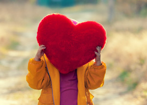 Little girl hiding behind heart shaped pillow and holding it in hands