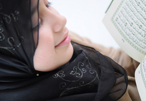 Little girl read holy Koran and smiles