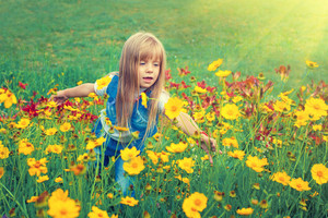 Little girl walking on flower lawn