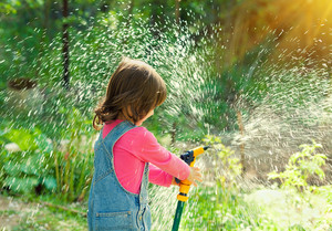 Little girl watering garden