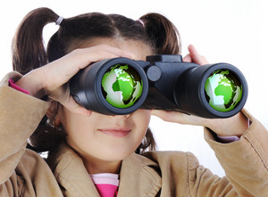 Little girl with binoculars, earth globe in glasses