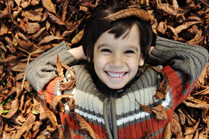 Little happy positive kid laying on fall ground and smiling, yellow and red leaves around him