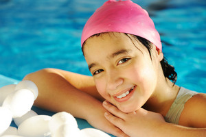 Little kid girl is swimming on pool