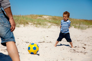 Little kid having fun and playing football with his dad on a summer vacation