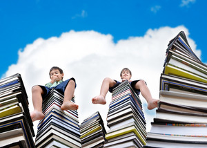 Little kids sitting on large stack of books