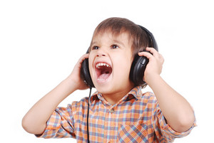 Little nice boy listening to music with peaceful expression on face