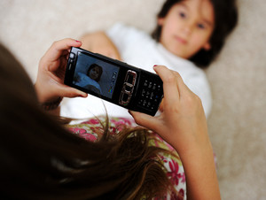 Little siste photographing her brother with digital mobile camera at home