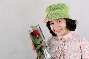 Little smiling girl with a rose