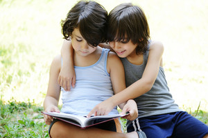 Little two boys reading a book in garden