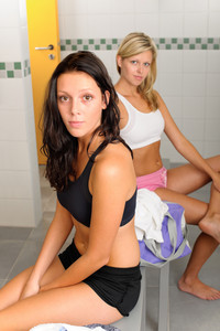 Locker room two sportive happy women sitting fitness training equipment