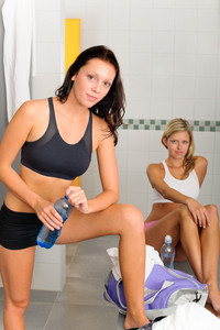 Locker room two sportive women getting ready fitness training equipment