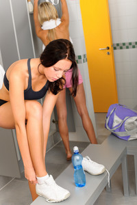 Locker room two sportive women getting ready for fitness training shower