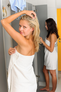 Locker room two sportive women wrapped in towel going shower
