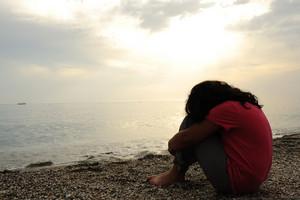Lonely sad girl on the dark beach
