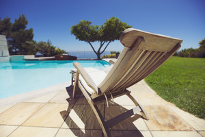 Long deck chair by the swimming pool. Empty wooden lounge chair next to pool at holiday resort.