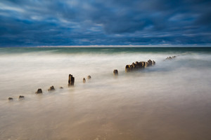 Long exposure breakwater photo. Baltic sea shore with old destroyed wooden brakwater.