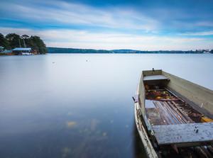 Long exposure landscape of lake shore with moored boats. Lake Krzywe in Olsztyn