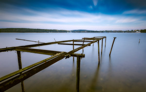 Long exposure landscape of lake shore with old destroyed steel construction (windlass for boats). Lake Krzywe in Olsztyn
