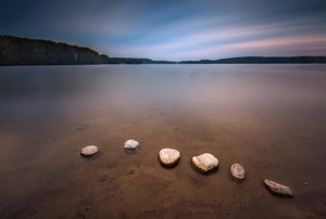 Long exposure landscape of lake shore with stones. Lake Krzywe in Olsztyn