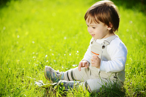 Lovely baby sitting on the green grass in the park and smiling for summer happy days