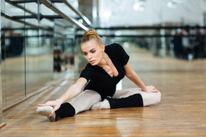 Lovely ballerina doing stretching exercises in ballet class