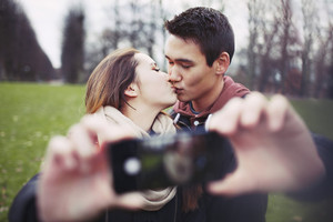 Lovely young couple taking self portrait while kissing at the park. Teenage boy and girl with smartphone outdoors.